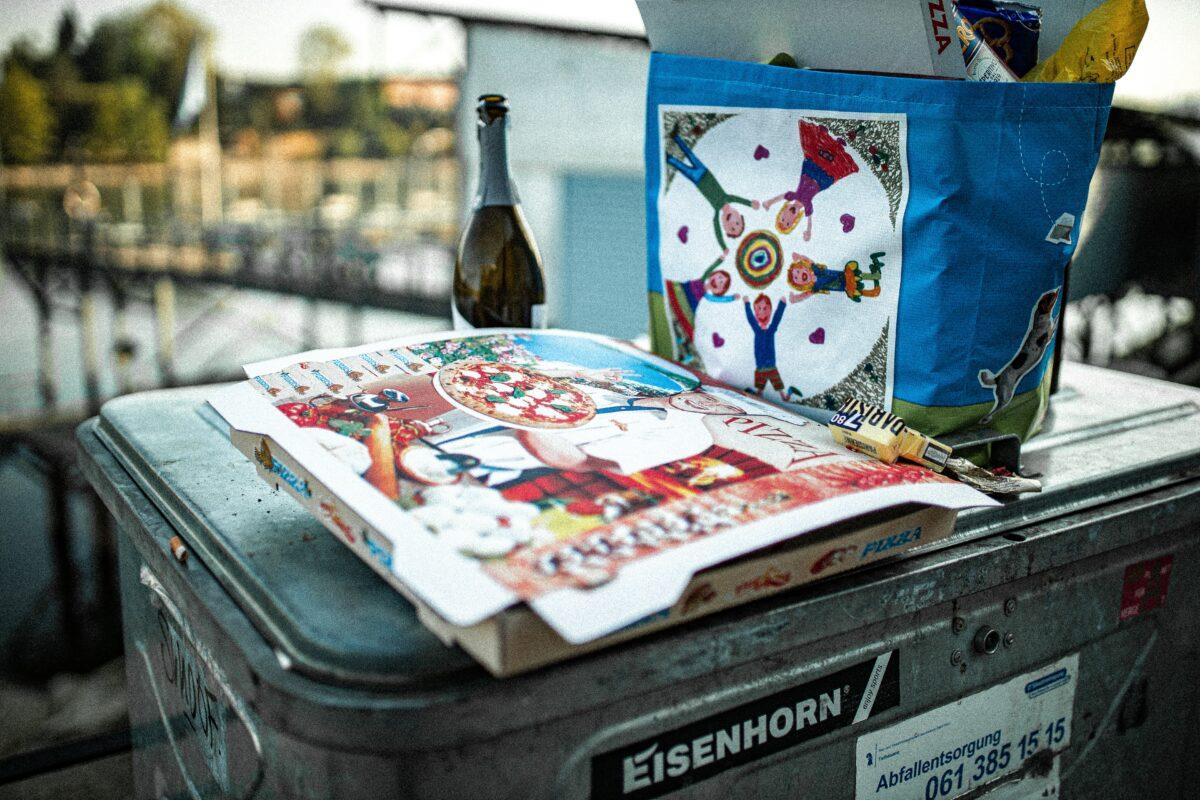 Pizzakarton und Flasche auf Mülleimer
